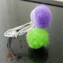 Ring mit Puschel in lila und grün